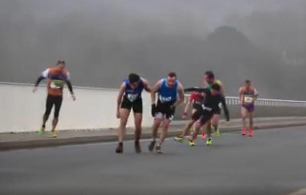 Capture d'écran de la vidéo d'Henry Dumoustier publiée sur Facebook où l'on voit des coureurs à pied lutter contre le vent près de Brest. – Capture d'écran Facebook