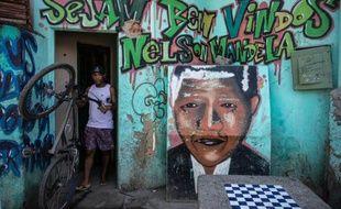 """""""Soyez bienvenus à Nelson Mandela"""" peut-on lire au-dessus d'un portrait graffité de Mandela sur le mur d'une maison marqué par des impacts de balles, à l'entrée d'une favela de la zone nord et pauvre de Rio."""