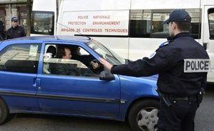 Un policier français arrête une voiture à Lyon le 14 mars 2014 pour vérifier son pot d'échappement