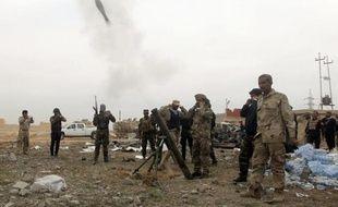 Des miliciens chiites lancent un obus de mortier vers des positions des jihadistes du groupe Etat islamique à Tikrit le 12 mars 2015