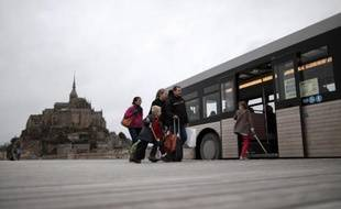 Des touristes montent à bord d'un bus, le 12 décembre 2014, pour se rendre au Mont-Saint-Michel par le nouveau pont-passerelle