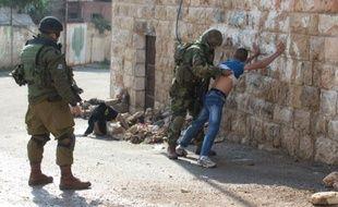 Des soldats israéliens fouillent un Palestinien, le 29 octobre 2015 à Hébron, en Cisjordanie