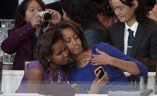 Les filles du président américain, Sasha (G) et Malia (D) Obama, prennent un «selfie» lors de la cérémonie d'investiture de leur père le 21 janvier 2013 à Washington.