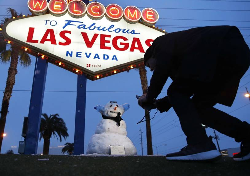 "A man, who declined to give his name, takes a picture of a small snowman at the ""Welcome to Fabulous Las Vegas"" sign along the Las Vegas Strip, Thursday, Feb. 21, 2019, in Las Vegas. Las Vegas is getting a rare taste of real winter weather, with significant snowfall across the metro area in the first event of its kind since record keeping started back in 1937. (AP Photo/John Locher)/NVJL101/19052566507904/1902211650"