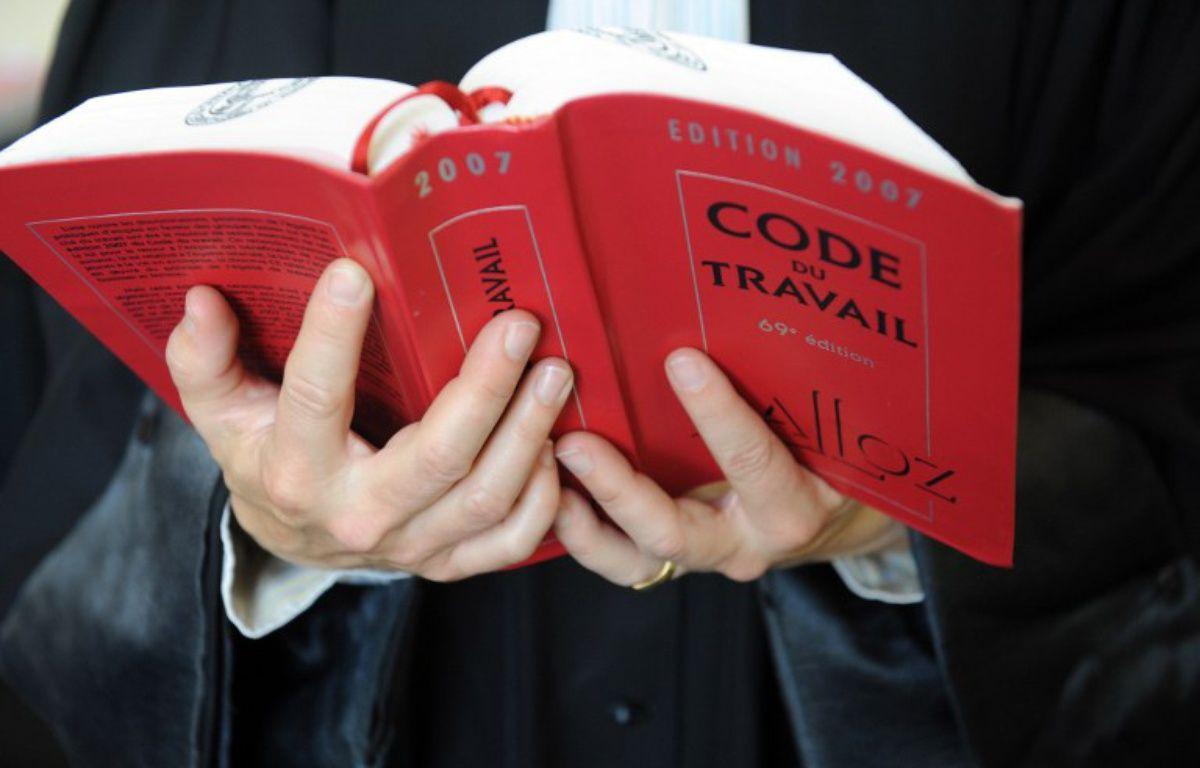 Un avocat tient le Code du travail. – FRED TANNEAU / AFP