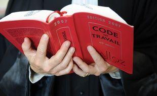 Un avocat tient le Code du travail.