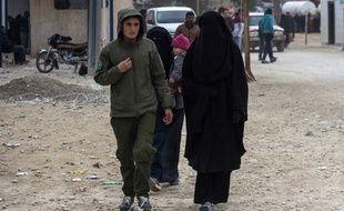 Un soldat kurde accompagne une femme dans le camp de réfugiés d'Al-Hol (image d'illustration).