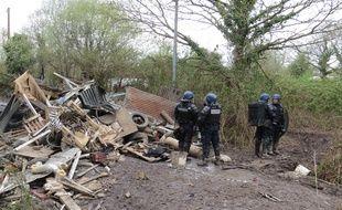 Des gendarmes devant les restes d'une cabane expulsée et détruite sur la ZAD.