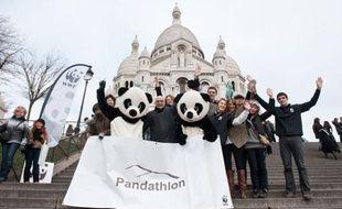 Serge Orru, directeur général du WWF France, entouré des deux pandas qui ont gravi la butte Montmartre le 25 janvier 2011.