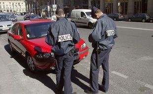 Deux policiers en train de mettre un PV de stationnement à un automobiliste.