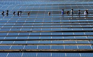 Les gens marchent entre les panneaux solaires lors de l'inauguration d'une ferme solaire à Giuncaggio le 8 octobre 2019, en Corse.