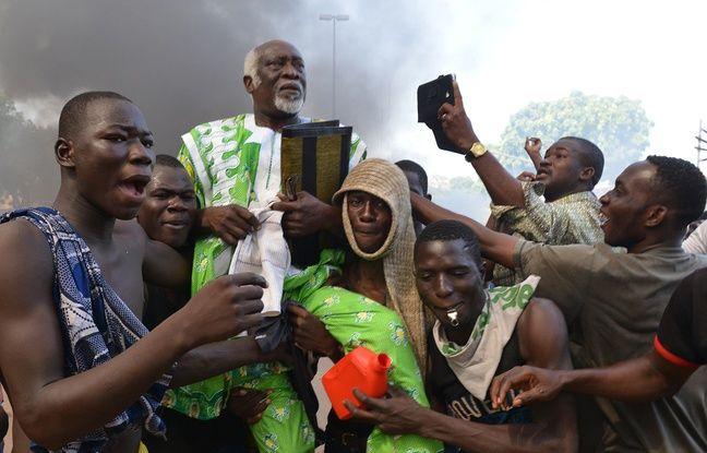 Des manifestants portent un élu de l'opposition devant le Parlement burkinabé à Ouagadougou, le 30 octobre 2014.