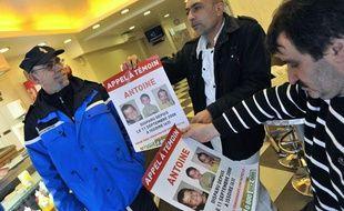 Des policiers distribuent des affiches à l'effigie du petit Antoine disparu à Issoire (Puy-de-Dôme) le 11 septembre 2008.