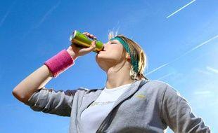 Jeune femme buvant une boisson energisante apres son jogging.