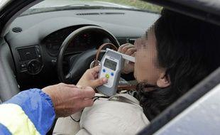 Une automobiliste subit un contrôle d'alcoolémie à l'aide d'un alcootest numérique.