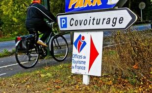 Un cycliste circulant à proximité d'une aire de covoiturage (illustration).