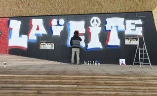 """Un street-artiste réalise une fresque """"laïcité"""" sur la Place de la laïcité à Paris le 9 décembre 2015."""