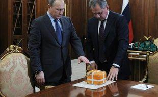 Le président Vladimir Poutine et le ministre russe de la Défense Sergei Shoigu examine la boîte noire du bombardier SU-24 abattu par la Turquie, le 8 décembre près de Moscou dans la résidence Novo-Ogaryovo