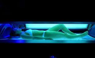 Une femmes fait une séance d'UV dans une cabinet de bronzage.