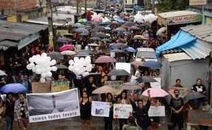"""Des centaines de personnes ont manifesté mardi dans le complexe de favelas de Maré à Rio de Janeiro pour dénoncer """"l'Etat qui tue"""" et la violence policière, lors d'un hommage aux victimes d'affrontements avec la police la semaine dernière."""