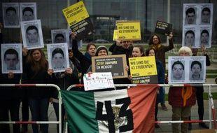 Des membres de l'organisation humanitaire Amnesty International, brandissent des photos d'étudiants disparus au Mexique, lors d'une manifestation à Berlin, devant la chancellerie, le 12 avril 2016