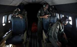 TO GO WITH: MALAYSIA-CHINA-VIETNAM-MALAYSIAAIRLINES-TRANSPORT-ACCIDENT,FOCUS BY SHANNON TEOH This picture taken on March 15, 2014 shows crew members looking outside windows from a Malaysian Air Force CN235 aircraft working during a search and rescue (SAR)Des membres de l'aviation malaisienne scrutent la mer lors des recherches le 15 mars 2014 au dessus du détroit de Malacca