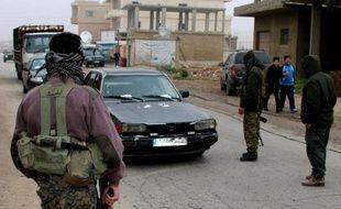 Des Chiites armés contrôlent des véhicules à Bazzalié, près de la frontière syrienne, après l'exécution d'un policier libanais par le Front Al-Nosra, le 6 décembre 2014