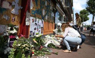 Devant le bar à Rouen, des passants rendent hommage aux 14 victimes du Cuba Libre, un an après les faits en 2017.