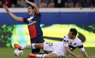 L'attaquant du PSG Edinson Cavani taclé par le défenseur toulousain Uros Spajic, le 28 septembre 2013, au Parc des Princes.