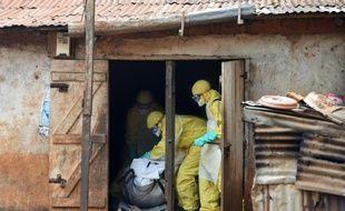 Des membres de la Croix-Rouge emportent le corps d'une victime d'Ebola à Freetown, le 12 novembre 2014