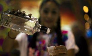 Une serveuse sert un shot de tequila (illustration).