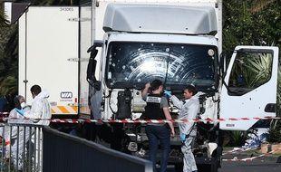 Des policiers à la recherche d'indices aux abords du camion qu'a lancé sur la foule un terroriste franco-tunisien de 31 ans, jeudi soir sur la promenade des Anglais, à Nice.
