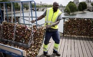 """Un employé enlève les """"cadenas d'amour"""" le 1er juin 2015 sur le Pont des Arts, à Paris"""
