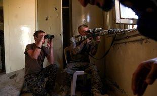 Un tireur d'élite américain et un combattant britannique gardent un poste à la périphérie de Raqa le 27 juin 2017; AFP PHOTO / DELIL SOULEIMAN