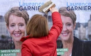 Une militante colle une affiche électorale pour la candidature de Laurence Garnier (LR) aux municipales 2020 à Nantes.