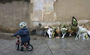 Un enfant devant des bouquets de fleurs déposés près du Carillon, un an après les attentats du 13-Novembre. LEWIS JOLY/SIPA