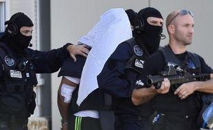 Yassin Salhi escorté par des polciers alors qu'il vient de récupérer son passeport dans son appartement de Saint-Priest avant d'être transféré à Paris, le 28 juin 2015