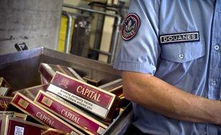 Un douanier devant un stock de cigarettes saisies