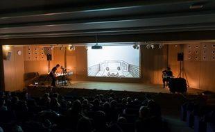 Jean-Charles Andrieu en plein dessin à gauche de la scène, Matthieu Chiara guitare à la main, à droite, avec l'écran de vidéoprojection au centre.