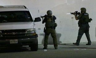 Des policiers vérifient une voiture à Dallas, le 8 juillet 2016 après la mort de cinq policiers