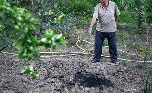 Un résident montre un cratère provoqué par un obus dans le village arménien d'Aygepar, sur la frontière entre l'Arménie et l'Azerbaïdjan, le 15 juillet 2020.