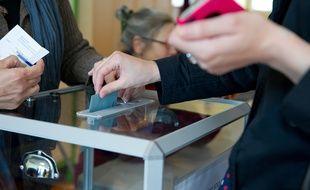 Une personne mettant une enveloppe dans une urne.