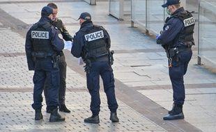 Des policiers, à Lille, contrôlent l'attestation de déplacement d'un homme