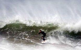 Un homme surfe près de Sydney alors que de gros orages sont attendus sur les cotes australiennes dans la journée, le 20 juin 2007.