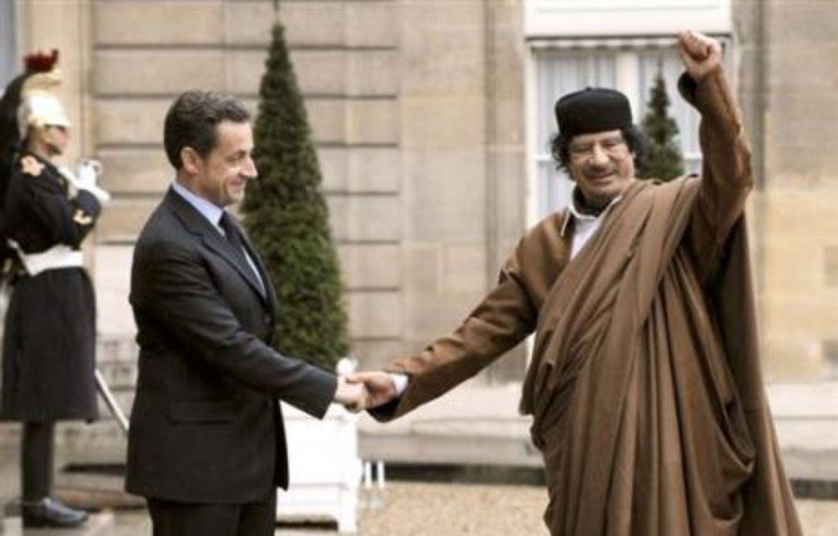 """Le dirigeant libyen Mouammar Kadhafi est arrivé lundi en début d'après-midi à l'aéroport parisien d'Orly pour une visite officielle de cinq jours en France qui déchaîne les critiques, jusqu'au sein du gouvernement, de ceux accusant Paris de sacrifier les principes pour armer le """"guide"""" libyen – Eric Feferberg AFP"""