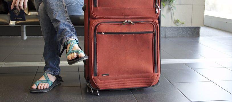 Illustration d'un voyageur assis près de sa valise.