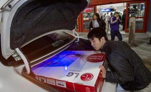 """Un consommateur fait rentrer un écran TV dans son coffre lors du """"Black Friday"""", le 27 novembre 2014, en Virginie (USA)."""