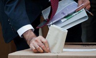 Un homme insère son bulletin dans l'urne, dans un bureau de vote de Bogota, le 9 mars 2014