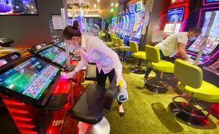 Des agents de nettoyage désinfectent les machines à sous au 3.14 Casino, à Cannes