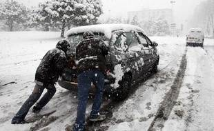 People push their car during a heavy snowfall in Marseille as winter weather continues in France January 7, 2009. Heavy snowfall in Marseille forced the international airport to close and paralysed all train and bus traffic on Wednesday in the country's second-biggest city.